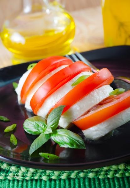 Помидор и сыр нарезаные на тарелке