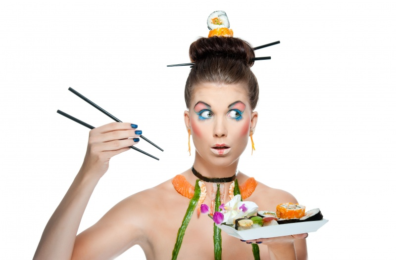 Женщина кушает суши палочками
