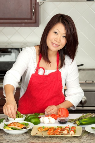 Красивая азиатская женщина готовит на кухне
