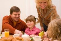 Мама з дітьми та чоловіком за столом