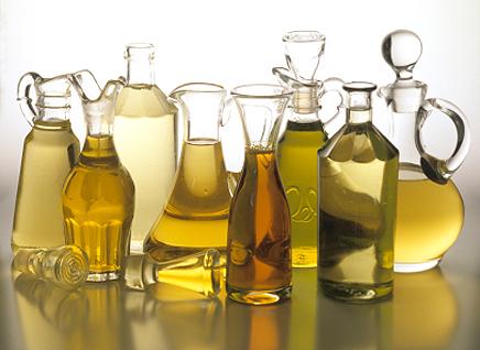 Олія в різних пляшках на столі