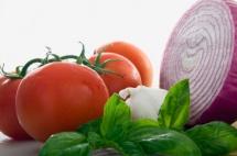 Надрізана цибуля та червоні помідори на світлому фоні