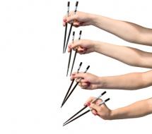 Композиція із 4-х рук з китайськими паличками на світлому фоні