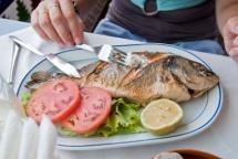 Риба приготовлена на грілі, овочі з зеленню та лаймою на тарілці