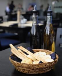Олія, хліб та мучні вироби в хлібному кошику на столі на кухні