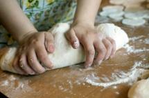 Мамині руки місять тісто на дошці