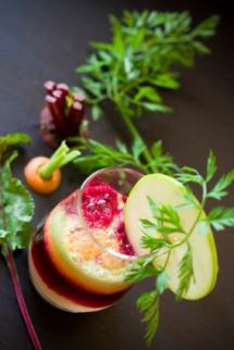 Склянка коктейлю з різними добавками та манго на столі