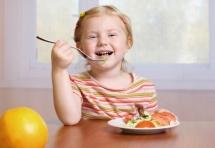 Портрет дитини з ложкою за обіднім столом з апельсином