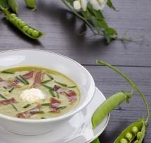 Густий суп з гороху на столі та стручки гороху поруч