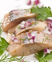 Нарізна маринована риба із зеленню петрушки на столі