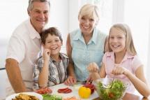 Родина за столом з дітьми біля овочів та салату