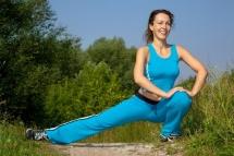 Жінка на природі з вправами аеробіки на розтяг