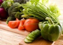 Зелень та нарізні огірки, помідори на столі