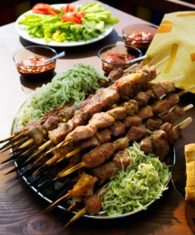 Шашлик з м'яса на шампурах та салат в тарілках