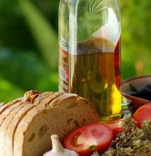 Хліб, часник, помідор та пів пляшки олії на зеленому трав'янистому фоні