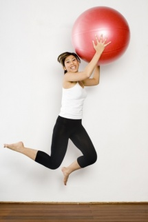 Спортсменка в стрибку з великим червоним м'ячем для фітнесу