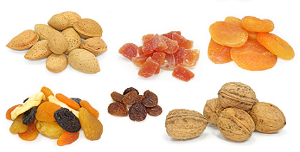 Сухофрукти, горіхи та насіння на столі на світлому фоні