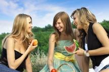Троє дівчат на природі з кошиком на фоні неба з кавуном та яблуком в руках