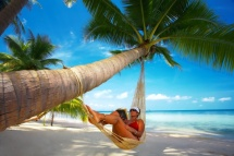 Жінка в гамаку під пальмою на пляжі на березі моря