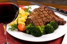 Бокал вина та просмажене м'ясо на тарілці