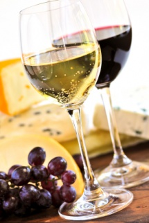 Два бокали вина, сир та виноград на світлому фоні