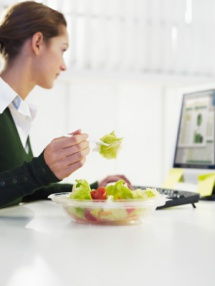 Жінка з салатом в офісі за комп'ютером