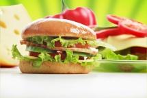 Гамбургер з хлібом та м'ясом та нарізний перець на задньому плані