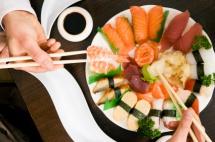Блюдо в китайському ресторані та палички в руці