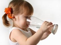 Маленька дівчинка п'є воду зі стакана