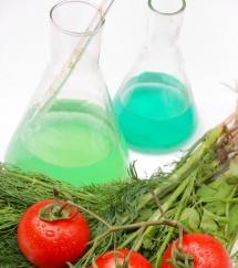 Два помідори, хімія в мензурках та зелень на білому столі