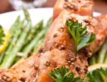 Печена риба з петрушкою на тарілці зі стручками гороху на задньому плані