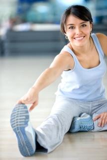 Жінка робить гімнастику з розтягуванням на підлозі