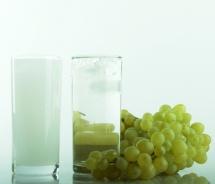 Стакан з горілкою та з араком і гілка винограду на столі