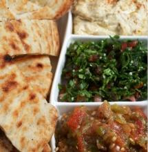 Закуски мезе з арабської кухні та коржі хліба на столі
