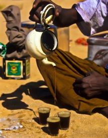 Чоловік сидячи на землі розливає на три порції каву з чайничка