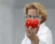 Портрет дослідника в білому халаті з помідором простягненим в кадр