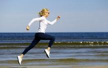 Спортсменка біжить на фоні моря з хвилями