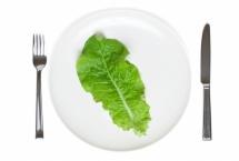 Листок зелені на тарілці зі столовим набором