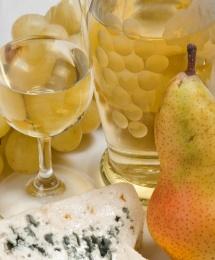Вино, виноград, сир із Франції та груша на світлому столі