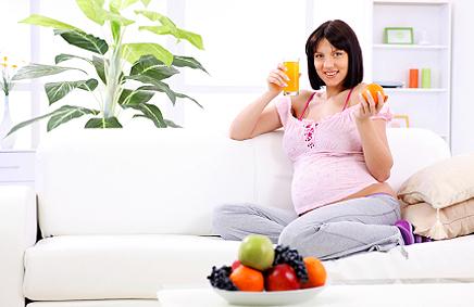 Вагітна жінка зі склянкою соку та апельсином на дивані