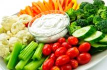 Капуста, інші свіжі овочі та піала соусу на блюді на столі