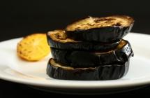 Нарізні печені баклажани на тарілці на чорному фону