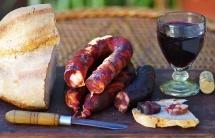 Хліб, ковбаса з червоного м'яса та вино на кухні на дошці