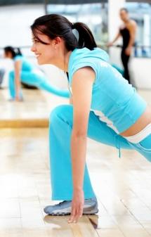Студентка в залі для фітнесу із вправами на розтягування м'язів ніг