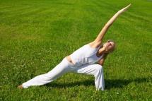 Жінка в полі на природі з вправами йоги на фоні зеленої трави